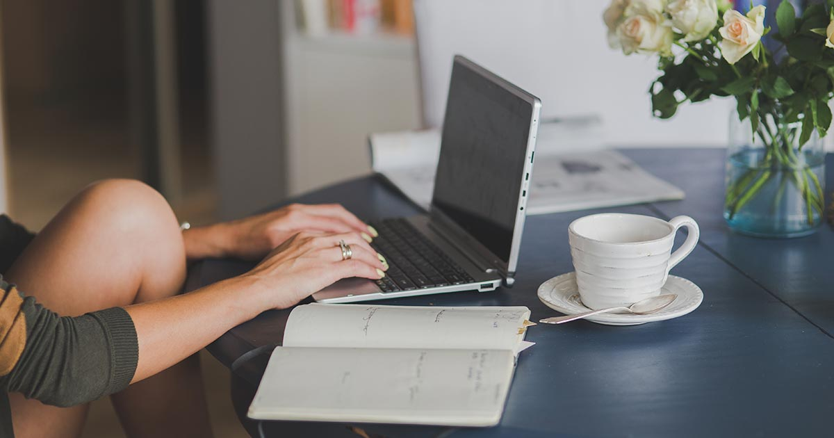 Woman typing on laptop with notebook and coffee on table