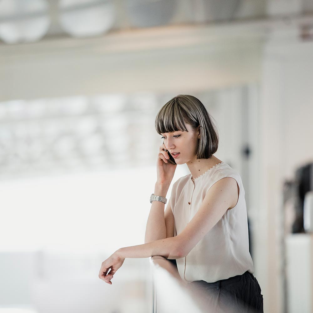 Woman leaning on metal bar in office on her phone